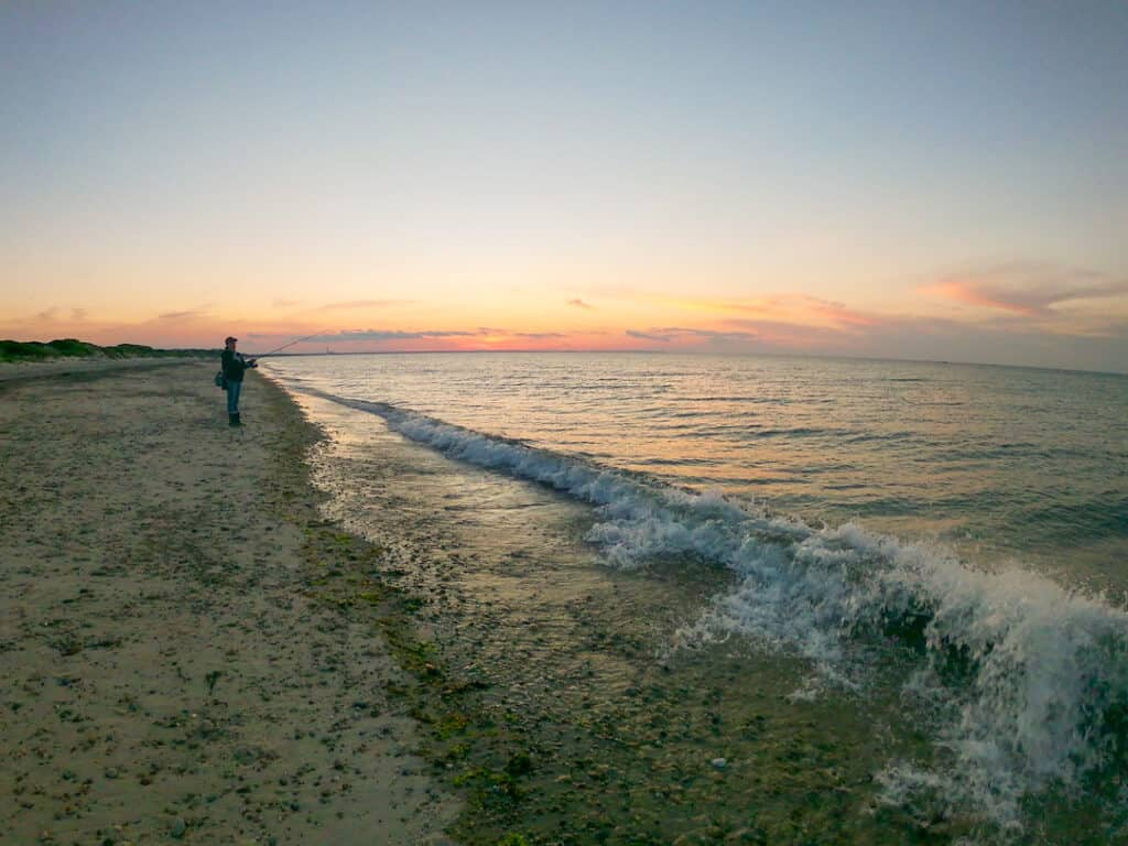 person fishing by the ocean - places to visit in New England