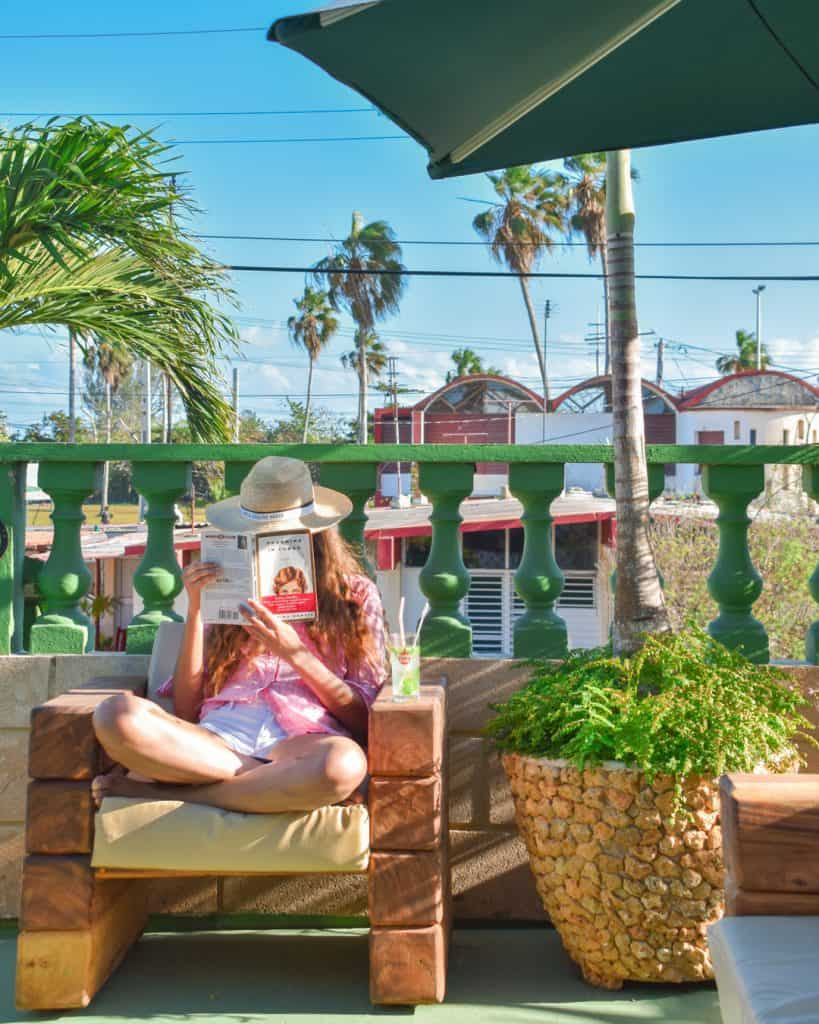 woman sitting on a porch reading a book - best places to stay in cuba