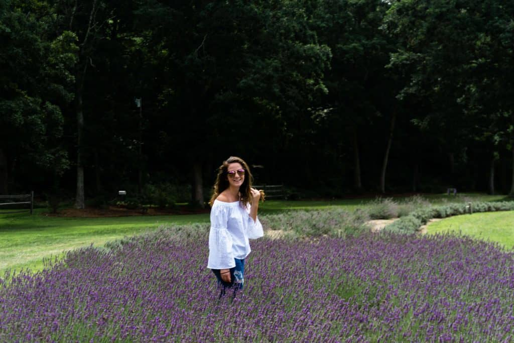 women smiling at the camer while standing in a lavender field - places to visit in New England