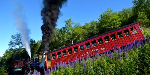 red railroad car being pushed by an old fashion steam engine - things to do in new england