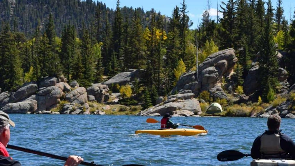 people kayaking near a rocky coastline - places to visit in New England